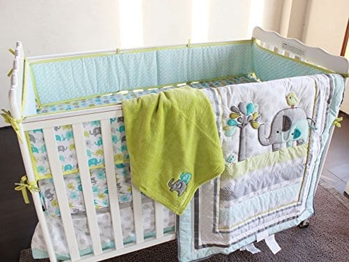 four piece crib bedding set in pastel colors with elephants and birds