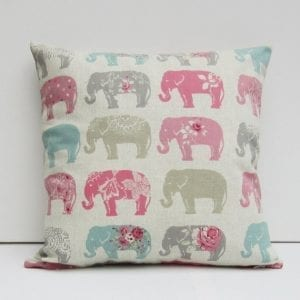 white cusion with repeating elephant print in pinks and greys