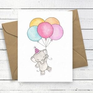 greetings card with elephant wearing party hat and holding balloons