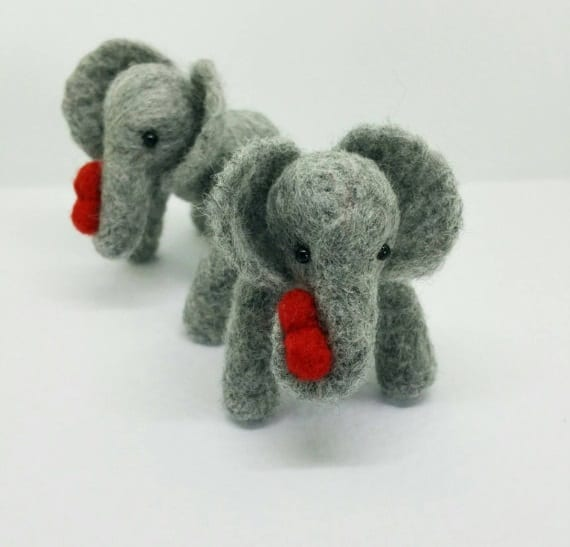 small needlefelted elephant holding a heart